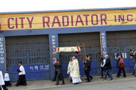 Archbishop Alexander Sample carries the Eucharist down Northwest Everett Street past a radiator shop in Portland, Ore., on the way to lead a rosary and exorcism for peace and justice in the city on Oct. 17, 2020. In popular culture, exorcism often serves as a plot device in chilling films about demonic possession. Recently, two Roman Catholic archbishops showed a different face of exorcism. They performed the rite in well-attended outdoor ceremonies to drive out any evil spirits lingering after acrimonious protests. In Portland, Oregon, Archbishop Alexander Sample led a procession of more than 200 people to a city park, then conducted an exorcism rite. The event followed more than four months of racial-justice protests in Portland. (Ed Langlois/Catholic Sentinel via AP)