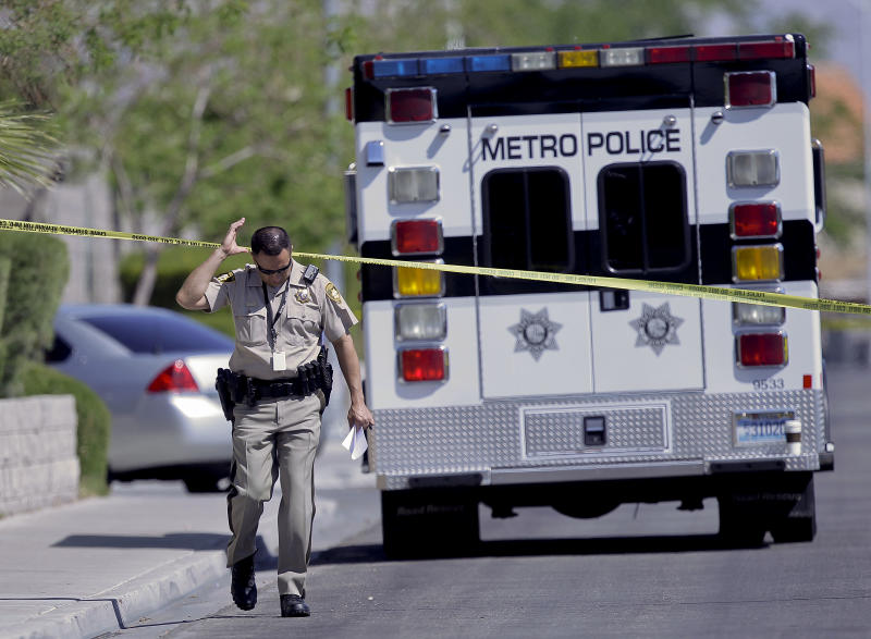 Las Vegas Metro police officer Jacinto Rivera ducks under crime scene tape outside a home where two bodies and an injured man were, Monday, April 16, 2012, in Las Vegas. Police are questioning a man covered in blood at the home where a 9-year-old boy told school officials his mother and sister were dead. (AP Photo/Julie Jacobson)