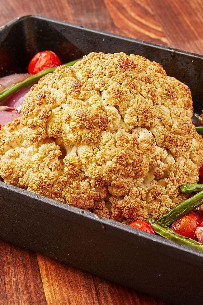 """<p>A whole roasted cauliflower makes for a fantastic vegetarian main dish. This one is roasted around extra veggies and has a slightly sweet balsamic glaze over it. It's easy to throw together and will leave you feeling full, not heavy.</p><p>Get the <a href=""""https://www.delish.com/uk/cooking/recipes/a33948230/balsamic-glazed-roasted-cauliflower-recipe/"""" rel=""""nofollow noopener"""" target=""""_blank"""" data-ylk=""""slk:Balsamic Glazed Roasted Cauliflower"""" class=""""link rapid-noclick-resp"""">Balsamic Glazed Roasted Cauliflower</a> recipe.</p>"""