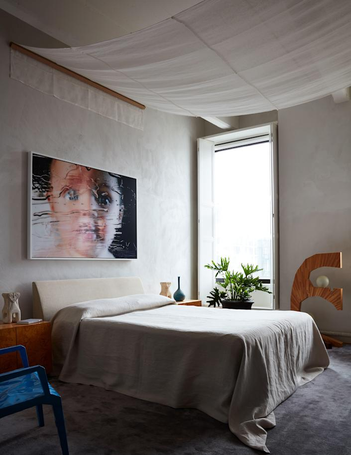 In the plaster-walled master bedroom, a Marilyn Minter portrait of the couple's son hangs above the Jasper Morrison bed, with its canopy of Schumacher fabric, custom bedspread of Belgian linen from Cowtan & Tout. Valle designed the straw marquetry light, and the blue chair is by François Azambourg. Stark rug.