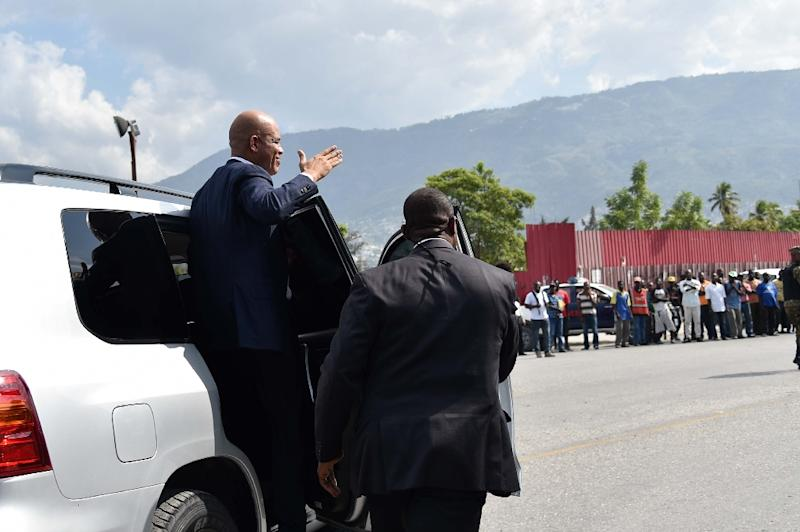 Haitian President Michel Martelly greets supporters as he departs the Parliament after delivering his farewell speech on February 7, 2016 in Port-au-Prince (AFP Photo/Hector Retamal)
