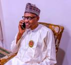 Nigerian President Muhammadu Buhari speaks on the phone with Katsina state Governor Aminu Bello Masari