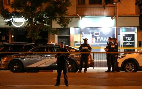 Police are seen near the scene of a mass shooting in Toronto - Credit: CHRIS HELGREN/Reuters