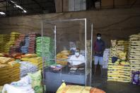 A Sri Lankan trader waits for customers adhering to health guidelines given by the authorities to curb the spread of coronavirus at a wholesale market in Welisara, outskirts of Colombo, Sri Lanka, Monday, May 31, 2021. (AP Photo/Eranga Jayawarden)