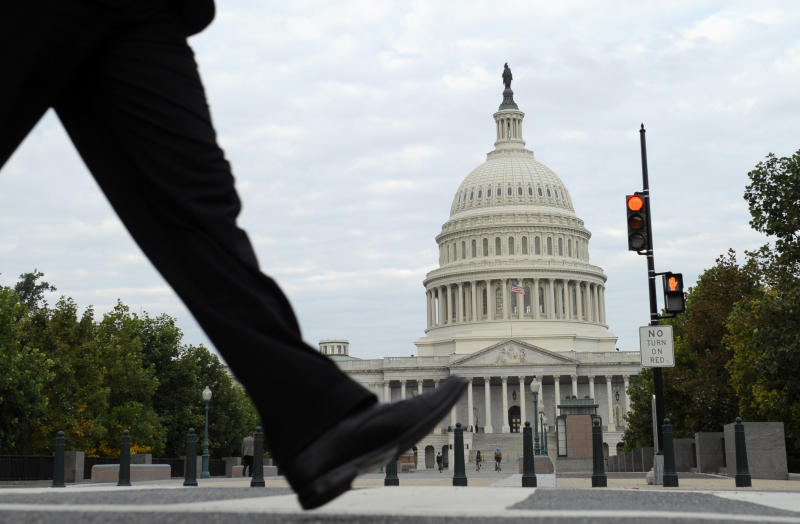 FILE - In this Tuesday, Oct. 1, 2013, file photo, people walk near Capitol Hill in Washington. As the government's partial shutdown enters a second day, most companies across the country are doing business as usual. Yet concern is rising that a prolonged shutdown would cause some work at private companies to dry up and consumers to lose faith in the U.S. economy. (AP Photo/Susan Walsh, File)