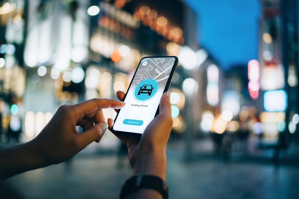 Close up of young woman using mobile app device on smartphone to arrange a taxi ride in downtown city street, with illuminated city traffic scene as background