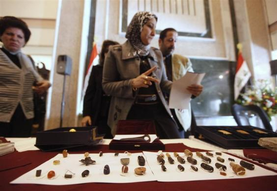 An employee checks recovered artifacts at the Iraqi Ministry of foreign Affairs headquarters in Baghdad January 30, 2012. A 6,500-year-old Sumerian gold jar, the head of a Sumerian battle axe and a stone from an Assyrian palace were among 45 relics returned to Iraq by Germany. The items were among thousands stolen from Iraq's museums and archaeological sites in the mayhem that followed the U.S.-led invasion that ousted Saddam Hussein in 2003.