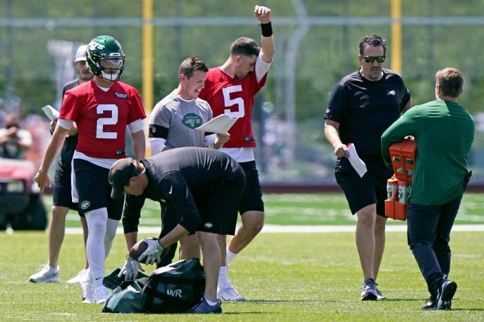 Quarterbacks Zach Wilson (2) and Mike White (5) take a break as offensive coordinator Mike LaFleur shouts out instructions during a break in an NFL football practice, Thursday, May 27, 2021, in Florham Park, N.J. (AP Photo/Kathy Willens)