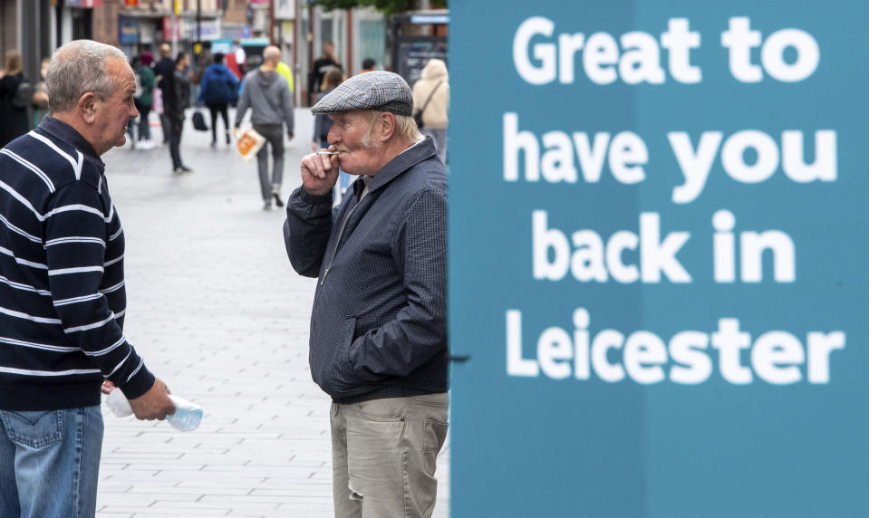 Two men have a discussion next to a sign in central Leicester, England, Monday June 29, 2020. The British government is reimposing lockdown restrictions in the central England city of Leicester after a spike in coronavirus infections, including the closure of shops that don't sell essential goods and schools. (Joe Giddens/PA via AP)