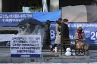"""A protester sits next to a statue symbolizing a wartime sex slave to demand full compensation and an apology for wartime sex slaves near the Japanese Embassy in Seoul, South Korea, Friday, Jan. 8, 2021. A South Korean court on Friday ordered Japan to financially compensate 12 South Korean women forced to work as sex slaves for Japanese troops during World War II, the first such ruling expected to rekindle animosities between the Asian neighbors. The sign reads """"Apology and Compensation."""" (AP Photo/Ahn Young-joon)"""