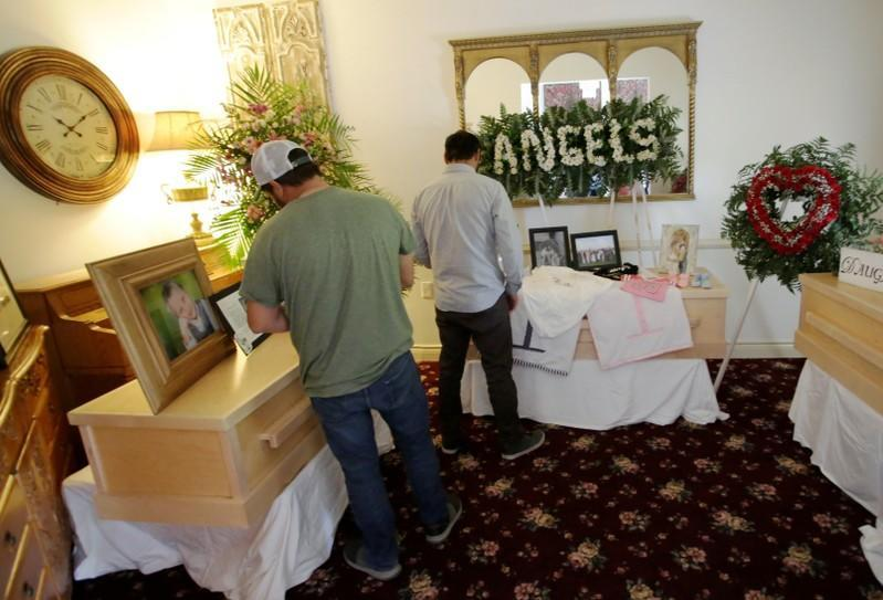 People stand next by the coffins of Rhonita Maria Miller and her four children, members of the Mexican-American Mormon community killed by unknown assailants, before their funeral in La Mora