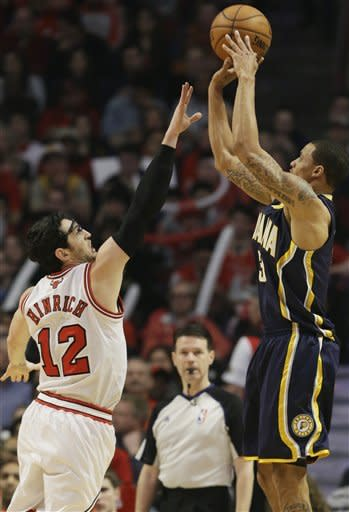 Indiana Pacers guard George Hill, right, shoots over Chicago Bulls guard Kirk Hinrich during the first half of an NBA basketball game in Chicago on Saturday, March 23, 2013. (AP Photo/Nam Y. Huh)