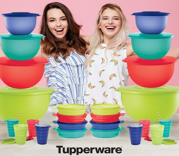 Two people in front of table with roughly 2 dozen Tupperware containers.