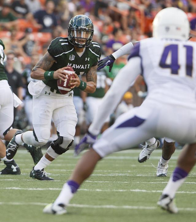 Hawaii quarterback Ikaika Woolsey (11) looks for an open receiver as Washington linebacker Travis Feeney (41) tracks Woosley during the second quarter of an NCAA college football game, Saturday, Aug. 30, 2014, in Honolulu. (AP Photo/Eugene Tanner)