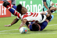 In this Friday, Sept. 20, 2019, file photo, Japan's Kotaro Matsushima, top, makes an attempt to score a try, tackled by Russia's Vasily Artemyev during the Rugby World Cup Pool A game at Tokyo Stadium between Russia and Japan in Tokyo. The try was disallowed by video referee. (AP Photo/Eugene Hoshiko, File)