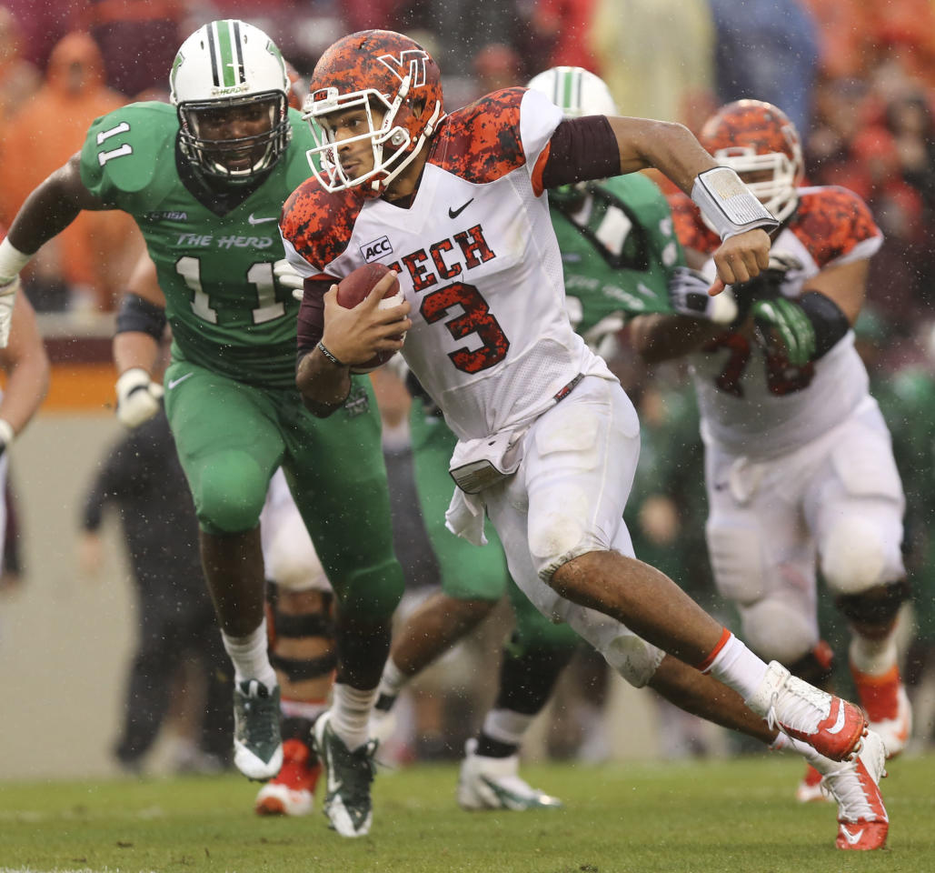 Virginia Tech quarterback Logan Thomas (3) runs for yardage past Marshall defender James Rouse, left, during the overtime period of an NCAA college football game Saturday, Sept. 21 2013,  in Blacksburg, Va. (AP Photo/The Roanoke Times, )
