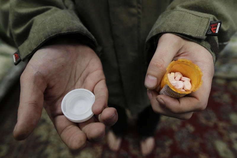 "In this Nov. 14, 2019 photo, Jon Combes holds his bottle of buprenorphine, a medicine that prevents withdrawal sickness in people trying to stop using opiates, as he prepares to take a dose in a clinic in Olympia, Wash. The clinic is working to spread a philosophy called ""medication first,"" which scraps requirements for counseling, abstinence or even a commitment to recovery in the battle against addictions to heroin and other opioids. (AP Photo/Ted S. Warren)"