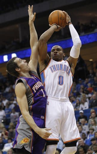 Oklahoma City Thunder guard Russell Westbrook (0) shoots in front of Phoenix Suns guard Goran Dragic (1) during the first quarter of an NBA preseason basketball game in Tulsa, Okla., Friday, Oct. 19, 2012. (AP Photo/Sue Ogrocki)