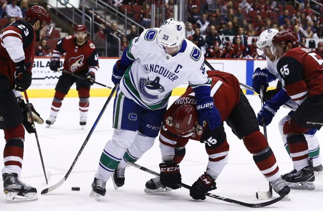 Arizona Coyotes defenseman Oliver Ekman-Larsson (23) gets to the puck as Vancouver Canucks center Henrik Sedin (33) battles with Coyotes center Brad Richardson (15) while Coyotes defenseman Jason Demers (55) and Canucks left wing Daniel Sedin (22) look on during the first period of an NHL hockey team Sunday, March 11, 2018, in Glendale, Ariz. (AP Photo/Ross D. Franklin)