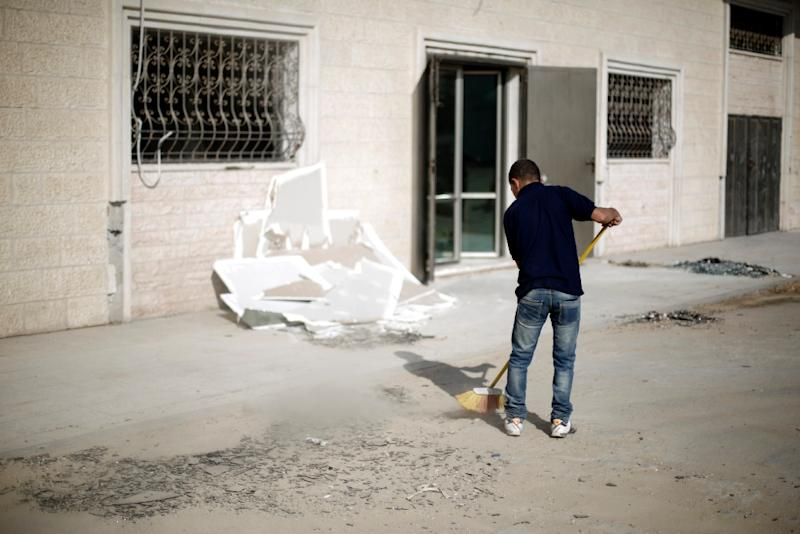 A Palestinian boy cleans debris near a training base of the Ezzedine al-Qassam brigades in Gaza City, after Israeli warplanes struck multiple militant targets in Gaza City, on June 4, 2015 (AFP Photo/Mohammed Abed)