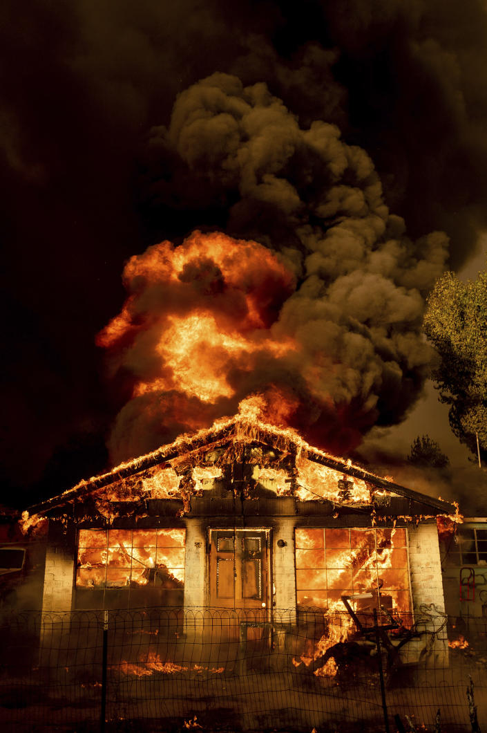 Flames consume a home as the Sugar Fire, part of the Beckwourth Complex Fire, tears through Doyle, Calif., Saturday, July 10, 2021. Pushed by heavy winds amid a heat wave, the fire came out of the hills and destroyed multiple residences in central Doyle. (AP Photo/Noah Berger)