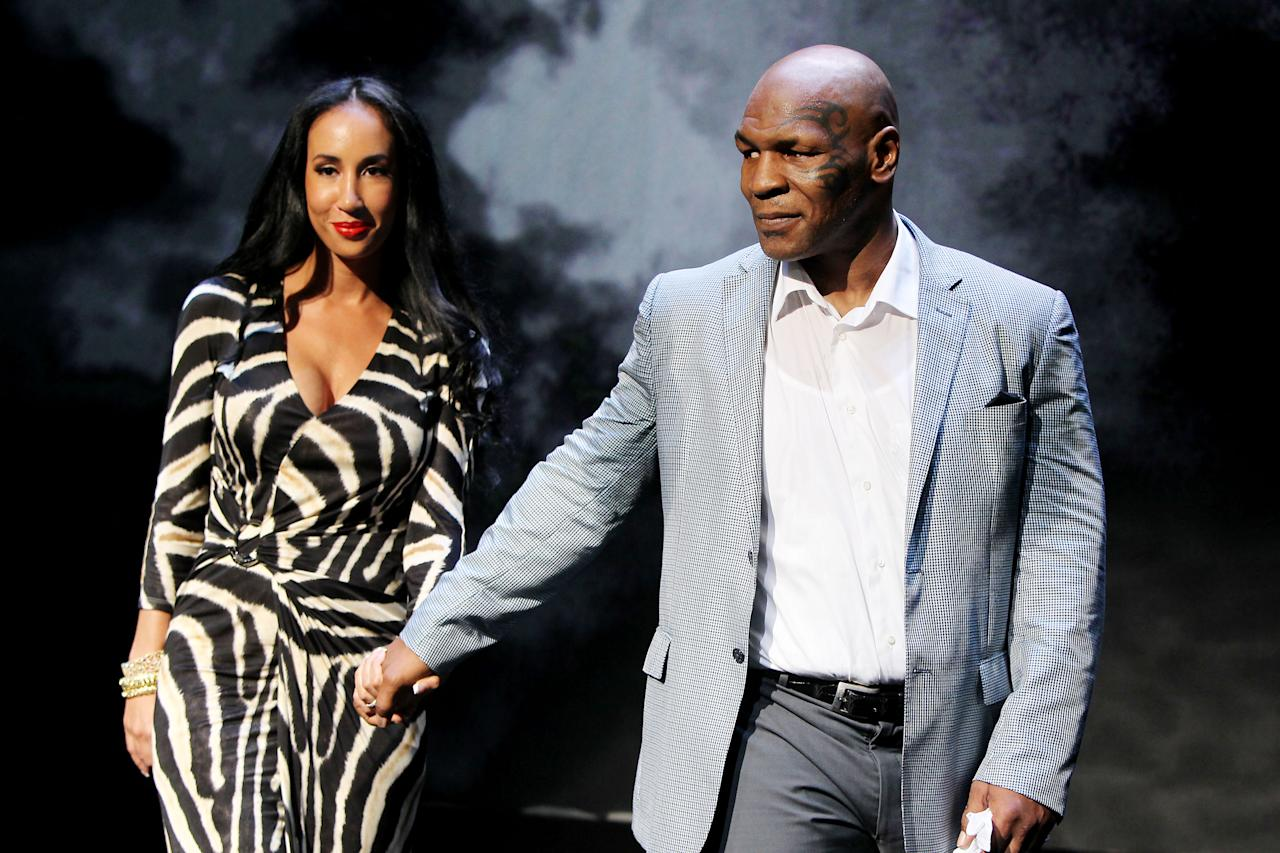 """This image released by Starpix shows, former boxer Mike Tyson, right, and his wife Kiki Tyson at the curtain call for the opening night of """"Mike Tyson: Undisputed Truth,"""" Thursday, Aug. 2, 2012 at the Longacre Theatre in New York.  The one man show starring Tyson was directed by Spike Lee, and written by Kiki Tyson. (AP Photo/Starpix, Amanda Schwab)"""