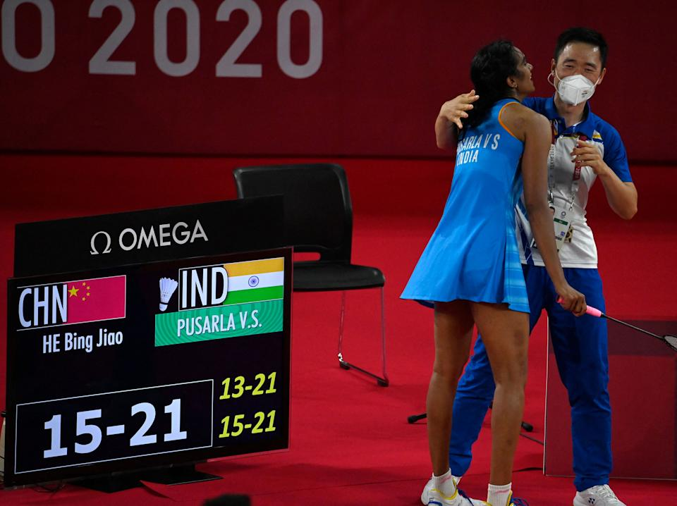 India's P. V. Sindhu (L) celebrates with a coach after beating China's He Bingjiao in their women's singles badminton bronze medal match during the Tokyo 2020 Olympic Games at the Musashino Forest Sports Plaza in Tokyo on August 1, 2021. (Photo by Alexander NEMENOV / AFP) (Photo by ALEXANDER NEMENOV/AFP via Getty Images)