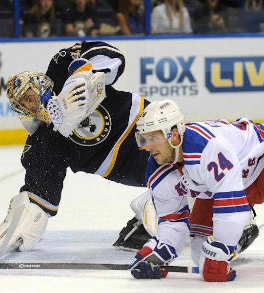 St. Louis Blues' goalie Jaroslav Halak, left, of Slovakia, defends against New York Rangers' Ryan Callahan (24) during the first period of an NHL hockey game on Saturday, Oct. 12, 2013, in St. Louis. (AP Photo/Bill Boyce)