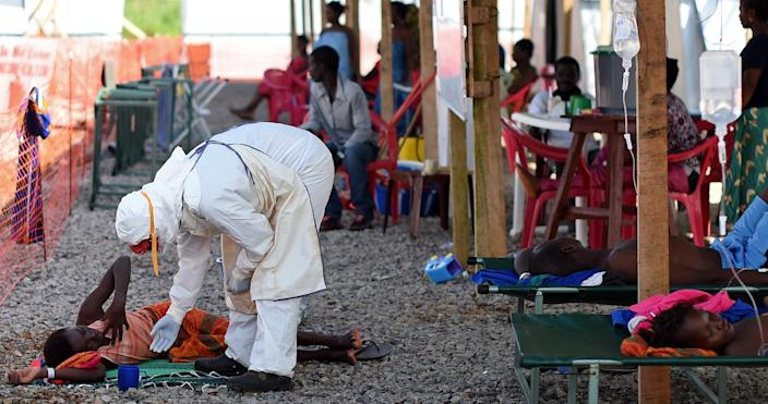 A nurse wearing personal protective equipment checks on a patient at the Kenama Ebola treatment center run by the Red Cross Society on November 15, 2014 (AFP Photo/Francisco Leong)