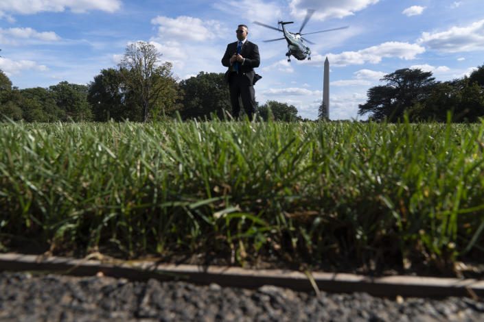 A Secret Service agent stands guard as Marine One with President Joe Biden abroad lifts off from the South Lawn of the White House in Washington, Monday, Sept. 20, 2021, for a short trip to Andrews Air Force Base, Md., and then on to New York ahead of a United Nations General Assembly meeting. (AP Photo/Andrew Harnik)