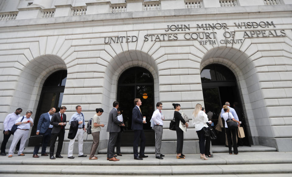 """FILE - In this Tuesday, July 9, 2019 file photo, People wait in line to enter the 5th Circuit Court of Appeals to sit in overflow rooms to hear arguments in New Orleans. The """"individual mandate"""" of former President Barack Obama's health care law is invalid, but other parts of the law need further review, a federal appeals court ruled Wednesday, Dec. 18, 2019. (AP Photo/Gerald Herbert, File)"""
