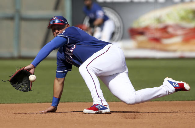 FILE - In this Wednesday, March 6, 2019, file photo, Texas Rangers third baseman Asdrubal Cabrera fields a ball hit by San Francisco Giants' Mac Williamson during the fourth inning of a spring baseball game in Surprise, Ariz. Williamson was out at first. (AP Photo/Ross D. Franklin, File)