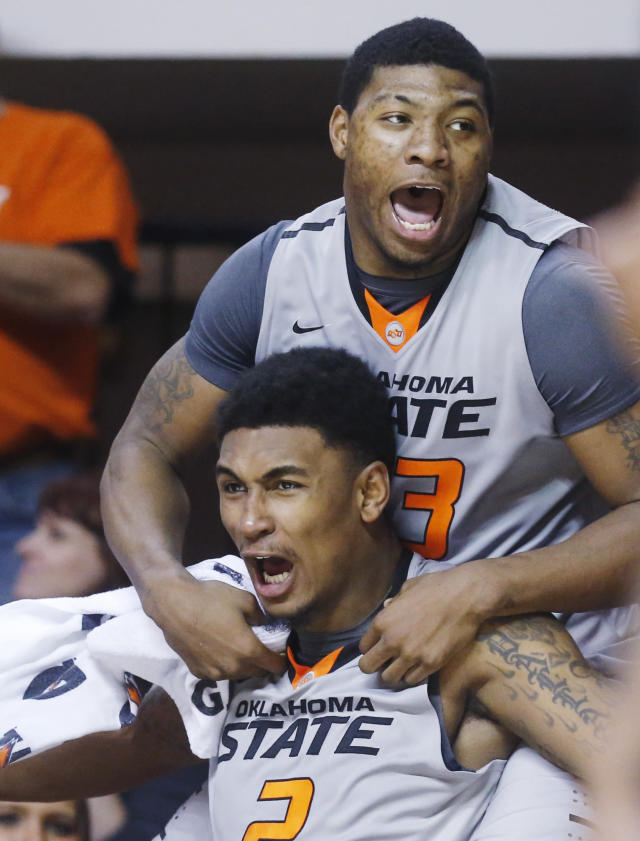 Oklahoma State wing Le'Bryan Nash (2) and guard Marcus Smart (33) clown around and celebrate on the bench in the second half of an NCAA college basketball game against Delaware State in Stillwater, Okla., Tuesday, Dec. 17, 2013. Oklahoma State won 75-43. (AP Photo/Sue Ogrocki)