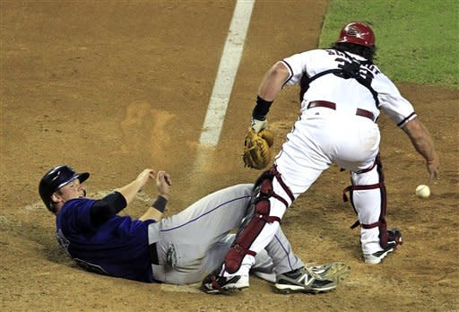 Colorado Rockies' DJ LeMahieu, left, scores a run as Arizona Diamondbacks' Konrad Schmidt (33) drops the ball during the 13th inning of a baseball game Monday, Oct. 1, 2012, in Phoenix.(AP Photo/Ross D. Franklin)