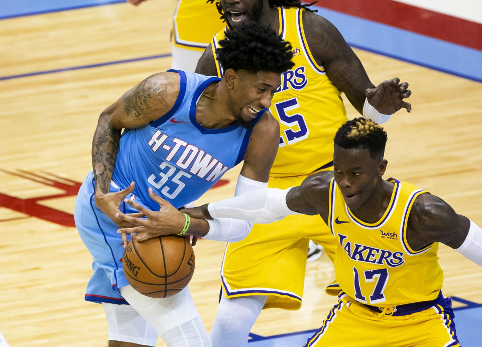 Houston Rockets center Christian Wood (35) loses the ball as he is defended by Los Angeles Lakers guard Dennis Schroeder (17) during the first quarter of an NBA basketball game Tuesday, Jan. 12, 2021, in Houston. (Mark Mulligan/Houston Chronicle via AP)