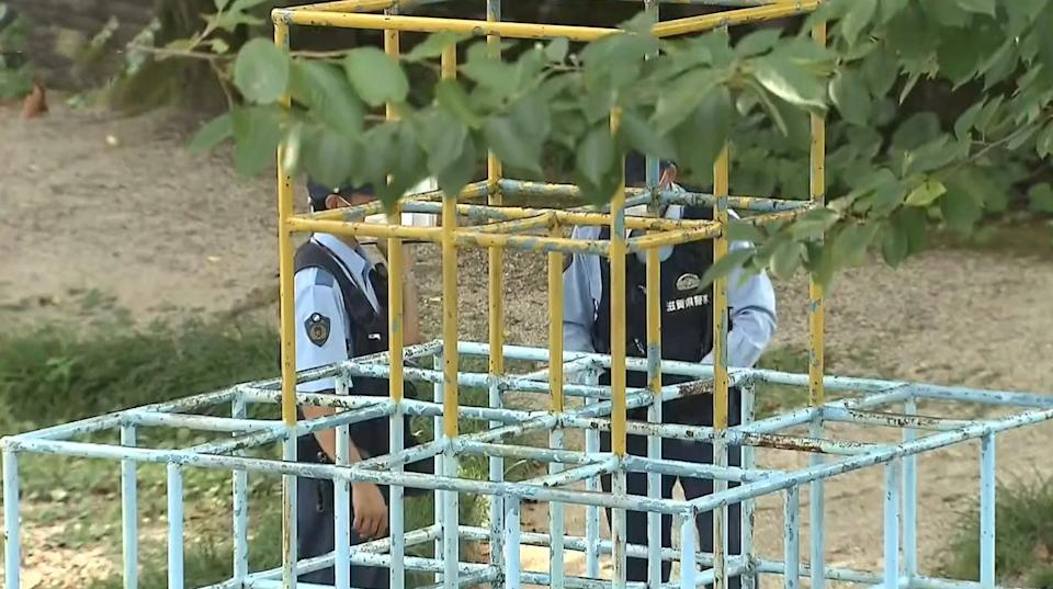 Two police officers stand next to a jungle gym in Japan where a little girl was found after she was allegedly killed by her brother.