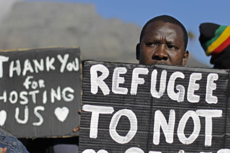 A protester holds a banner, left, reading 'Thank you for hosting us' during a demonstration in the city of Cape Town, South Africa, Wednesday, June 20, 2012. Protesters took to the streets to mark World Refugee Day and protest against the closure of the refugee reception office in Cape Town. (AP Photo/Schalk van Zuydam)