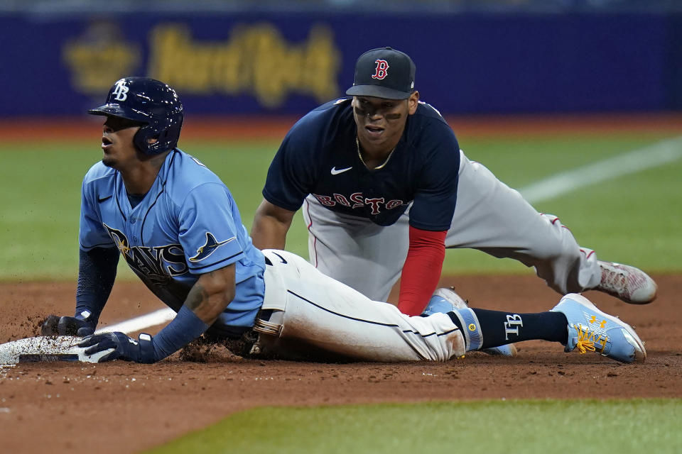 Tampa Bay Rays' Wander Franco, left, slides in safely to third base ahead of the tag by Boston Red Sox's Rafael Devers during the sixth inning of a baseball game Wednesday, June 23, 2021, in St. Petersburg, Fla. Franco went from first base to third on a single by Austin Meadows. (AP Photo/Chris O'Meara)