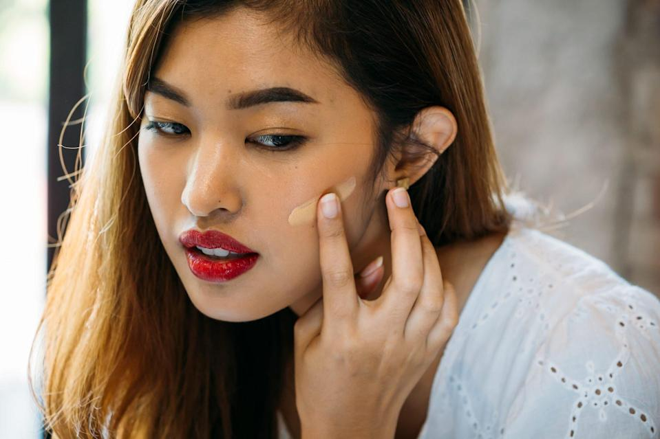 is-foundation-with-spf-enough: woman applying foundation