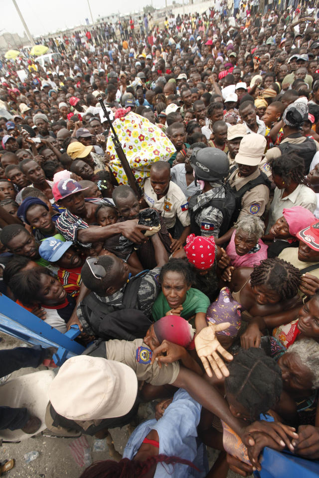 <p>Haitians surge the gates at a food distribution point in the Cite Soleil neighborhood in the aftermath of the Jan. 12 earthquake in Port-au-Prince, Tuesday, Jan. 26, 2010. (Photo: Gerald Herbert/AP) </p>