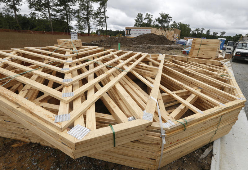 FILE - In this June 13, 2019, file photo stacks of building materials are stacked up near new home under construction in Mechanicsville, Va. On Friday, Aug. 23, the Commerce Department reports on sales of new homes in July. (AP Photo/Steve Helber, File)