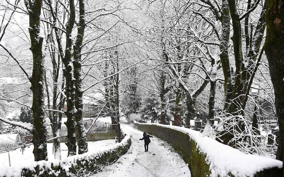 A person snowboards along a path in Marsden, northern England - OLI SCARFF/AFP