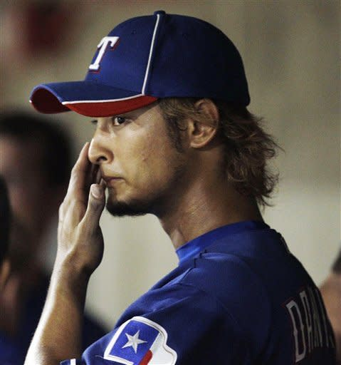 Texas Rangers starting pitcher Yu Darvish reacts in the dugout after giving up a home run to Colorado Rockies' Jason Giambi during the second inning of a spring training baseball game, Friday, March 30, 2012, in Scottsdale, Ariz. (AP Photo/Marcio Jose Sanchez)
