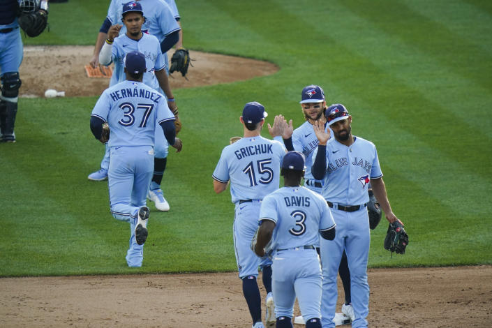 Toronto Blue Jays' Marcus Semien, right, and Bo Bichette, second from right, celebrates with teammates after the first game of a baseball doubleheader against the New York Yankees Thursday, May 27, 2021, in New York. The Blue Jays won 2-0.(AP Photo/Frank Franklin II)