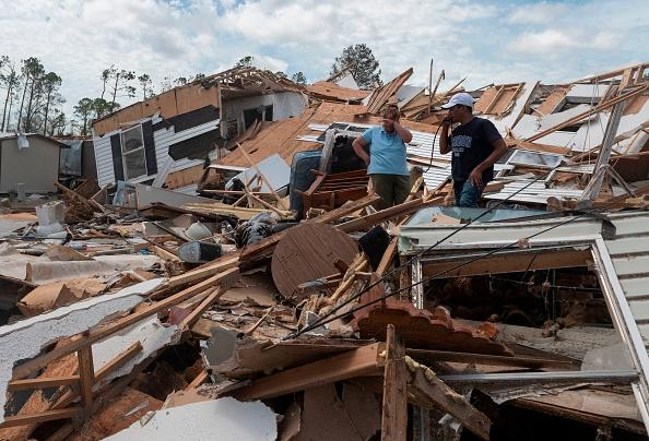 A couple react as they go through their destroyed mobile home following the passing of hurricane Laura in Lake Charles.