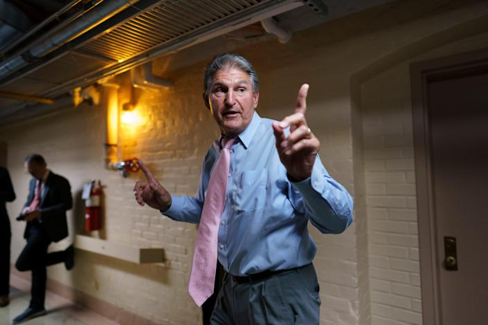 Sen. Joe Manchin, D-W.Va., an infrastructure negotiator, works with other Democrats in a basement room at the Capitol on June 16.