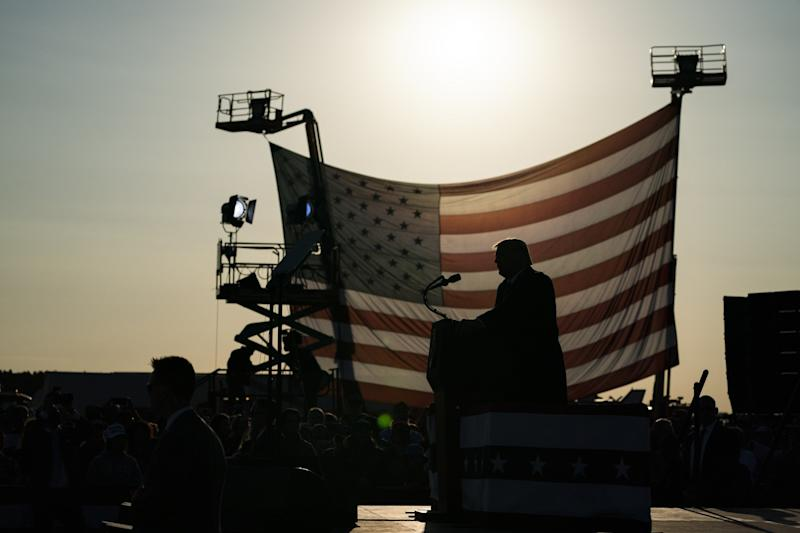 President Trump is silhouetted in front of a U.S. flag as the sun shines through