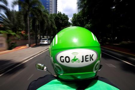FILE PHOTO: A Go-Jek driver rides a motorcycle on a street in Jakarta, Indonesia