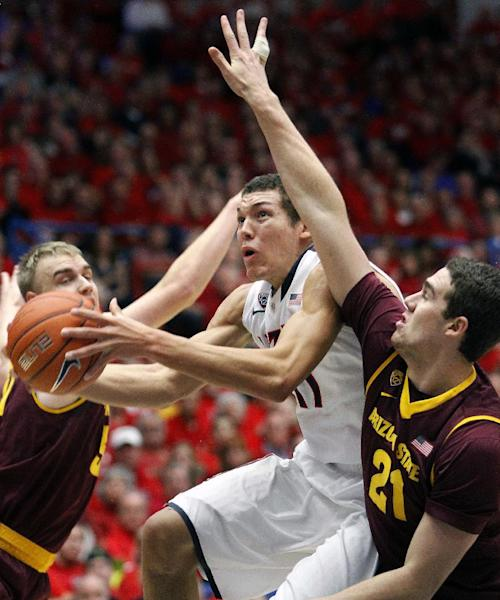 Arizona's Aaron Gordon, center, is sandwiched between Arizona's State's Jonathan Gilling, left, and Eric Koulechov (21) as he shoots for two points in the first half of an NCAA college basketball game on Thursday, Jan. 16, 2014, in Tucson, Ariz. (AP Photo/John Miller)