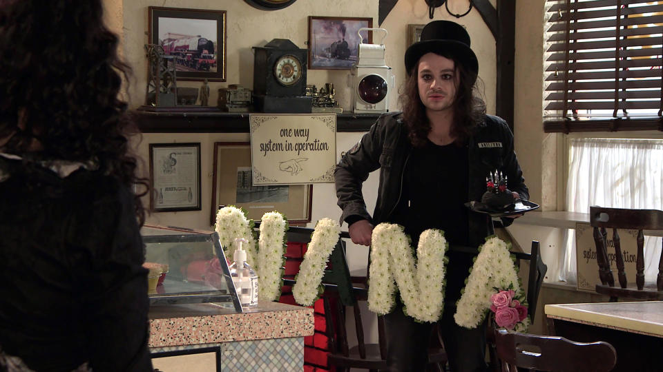 FROM ITVSTRICT EMBARGO - No Use Before  Tuesday 20th April 2021Coronation Street - Ep 10309Monday 26th April 2021 - 1st EpIn a bid to win Nina Lucas [MOLLIE GALLAGHER] round, Seb Franklin [HARRY VISINONI] calls at the cafe in full Goth attire and handing her a funeral wreath for her birthday, explains how George helped him achieve the look. Nina's furious and accuses him of making a mockery of her yet again. Picture contact David.crook@itv.com This photograph is (C) ITV Plc and can only be reproduced for editorial purposes directly in connection with the programme or event mentioned above, or ITV plc. Once made available by ITV plc Picture Desk, this photograph can be reproduced once only up until the transmission [TX] date and no reproduction fee will be charged. Any subsequent usage may incur a fee. This photograph must not be manipulated [excluding basic cropping] in a manner which alters the visual appearance of the person photographed deemed detrimental or inappropriate by ITV plc Picture Desk. This photograph must not be syndicated to any other company, publication or website, or permanently archived, without the express written permission of ITV Picture Desk. Full Terms and conditions are available on  www.itv.com/presscentre/itvpictures/terms